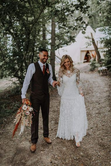 Boho Bride in Applique Wedding Dress with Long Sleeves and Groom in Wool Waistcoat Holding a Bouquet
