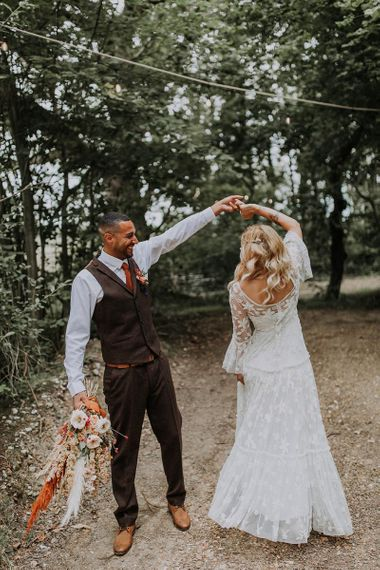 Groom in Wool Waistcoat  Twirling His Bride in a Lace Wedding Dress in the Woods