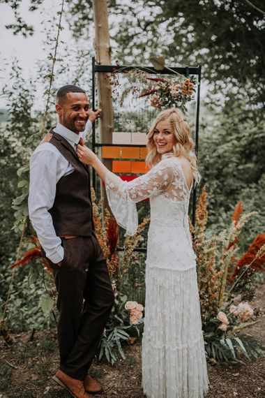 Boho Bride and Groom Standing Next to Their Extravagant Table Plan
