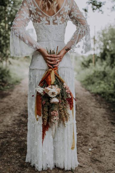Boho Bride in a Lace Wedding Dress Holding Her Natural Bouquet Behind Her Back