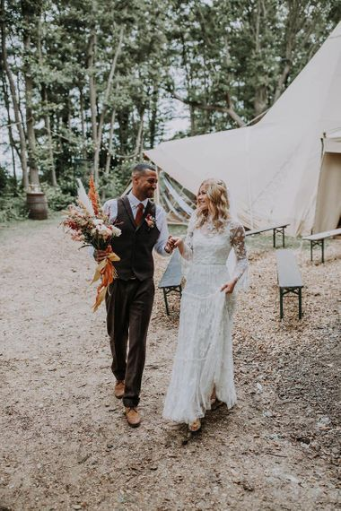 Boho Bride in Lace Wedding Dress with Long Sleeves and Groom in Wool Waistcoat Holding a Bouquet
