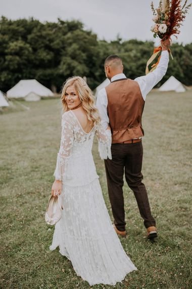 Boho Bride and Groom Walking Through the Fields Towards Their Bell Tent