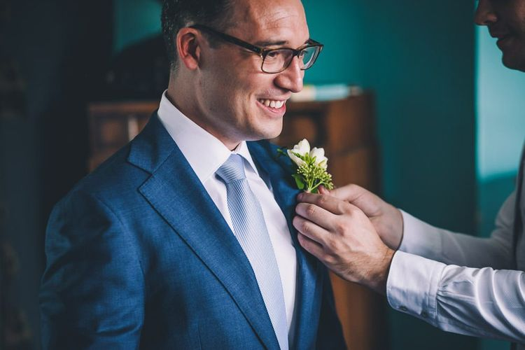 Groom getting ready for same-sex intimate city celebration in East London  wearing a navy blazer