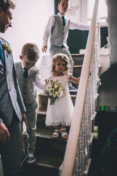 Young wedding guest with white bouquet at same-sex city celebration