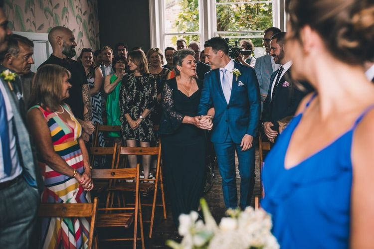 Groom walking down the aisle at The Roost Dalston Wedding Reception with vintage decor