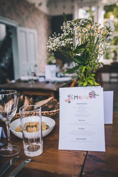 Personalised colourful menu at intimate city reception with vintage decor and eclectic touches