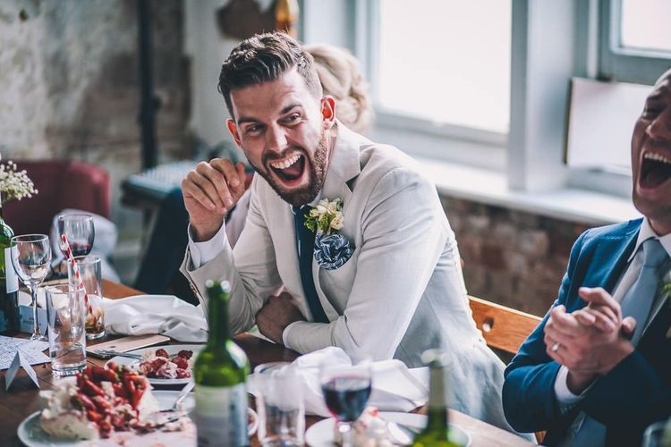 Grooms enjoying the speeches at same-sex intimate celebration in London