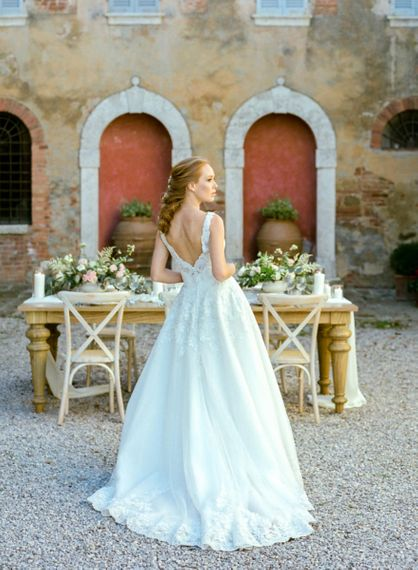 Bride in Lace Sorrisi di Gioia Wedding Dress Standing in Front of a Rustic Tablescape