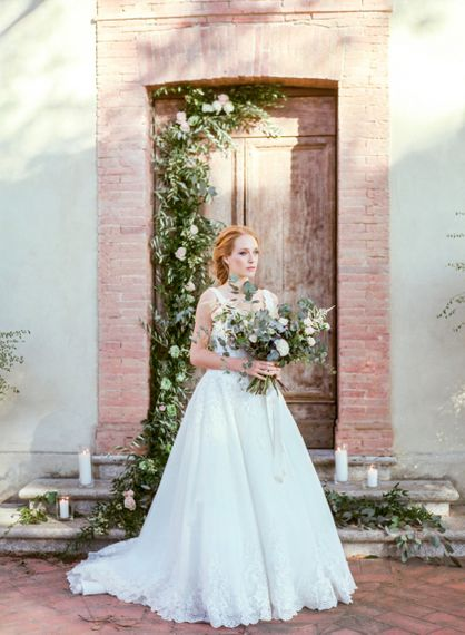 Bride Standing by a Floral Doorway in Lace Sorrisi di Gioia Wedding Dress Holding in a Eucalyptus  & Pink Rose Bouquet