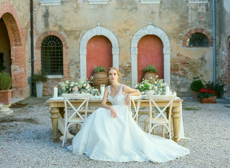 Bride in Lace Sorrisi di Gioia Wedding Dress Sitting in Front of a Rustic Tablescape