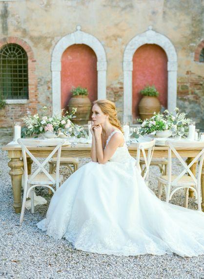 Bride in Lace Sorrisi di Gioia Wedding Dress Sitting at Rustic Tablescape