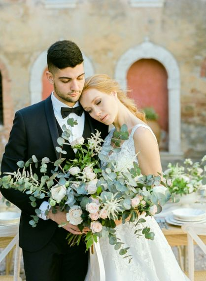 Bride in Lace Sorrisi di Gioia Wedding Dress and Groom in Black Tie Suit Holding an Oversized Wedding Bouquet