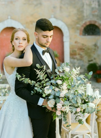 Bride with Natural Makeup in Lace Sorrisi di Gioia Wedding Dress and Groom in Black Tie Suit Holding an Oversized Wedding Bouquet