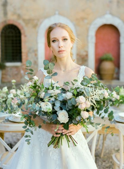 Bride in Lace Wedding Dress Holding a Romantic Wedding Bouquet with Eucalyptus, Ranunculus and Astilbe