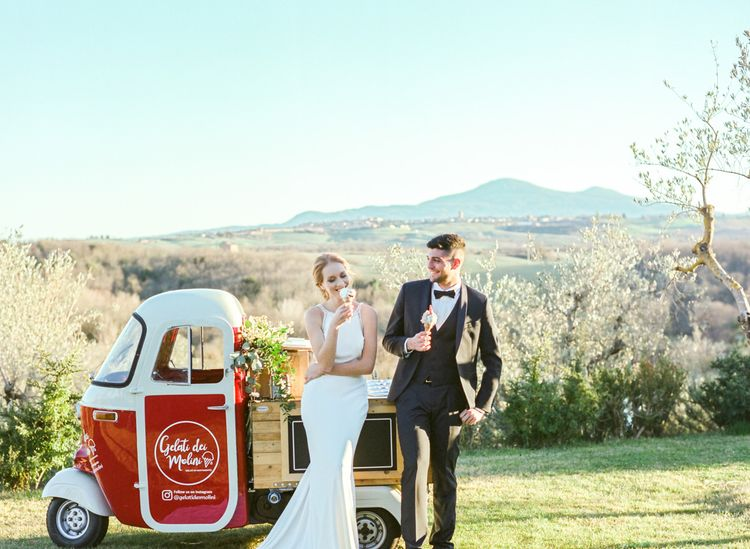 Bride in Lace Wedding Dress and Groom in Tuxedo Getting Ice-cream at a Gelato Truck