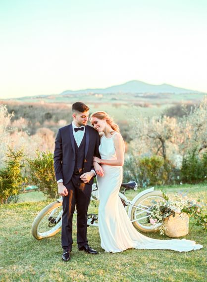Bride in Lace Wedding Dress and Groom in Tuxedo Embracing by a Vintage Bicycle