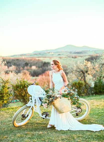 Bride in Lace Wedding Dress Standing Next to  a Vintage Bicycle Holding a Straw Bag of Flowers