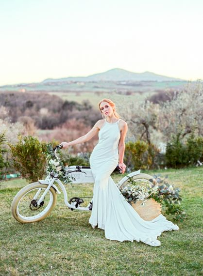 Bride in Lace Wedding Dress Standing Next to  a Vintage Bicycle