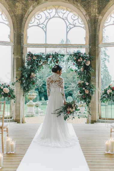 Bride at the Floral Arch Altar in Lace Bodice Suzanne Neville Wedding Dress | Blush & Burgundy Floral Fairytale Wedding Inspiration at Grittleton House Planned & Styled by Jennifer Louise Weddings | Katherine Yiannaki Photography