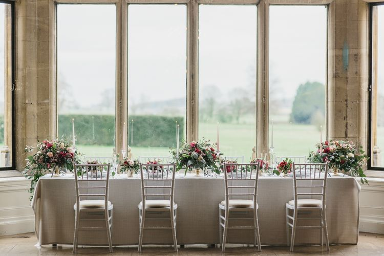 Reception Table with Taper Candles & Low Floral Arrangements | Blush & Burgundy Floral Fairytale Wedding Inspiration at Grittleton House Planned & Styled by Jennifer Louise Weddings | Katherine Yiannaki Photography