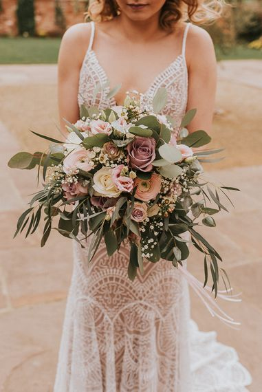 Bride in Lace Strappy Wedding Dress Holding a Romantic Oversized Bridal Bouquet with Pink and White Roses and Foliage