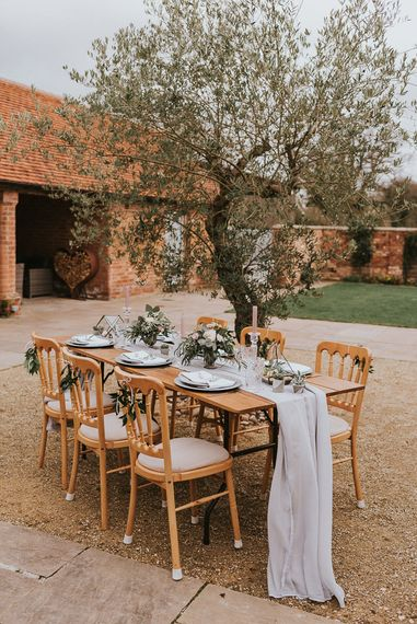 Intimate Tablescape Under an Olive Tree with Linen Table Runner, Taper Candles, Cut Glass and Romantic Flower Arrangements