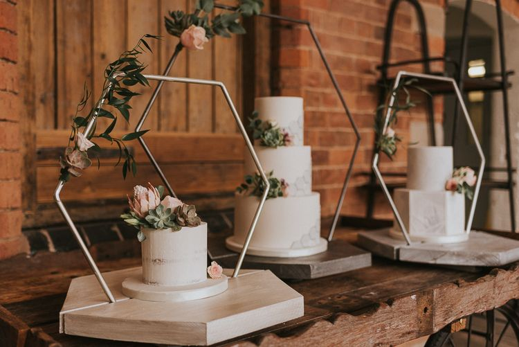 Three Wedding Cakes with Geometric Patterns on Hexagonal Cake Stand Frames
