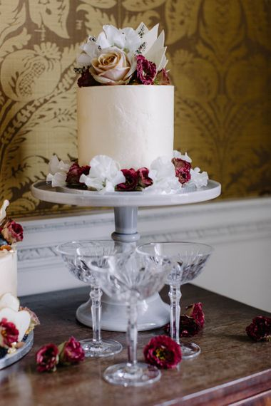 Single Tier Wedding Cake on Cake Stand with Floral Skirt.