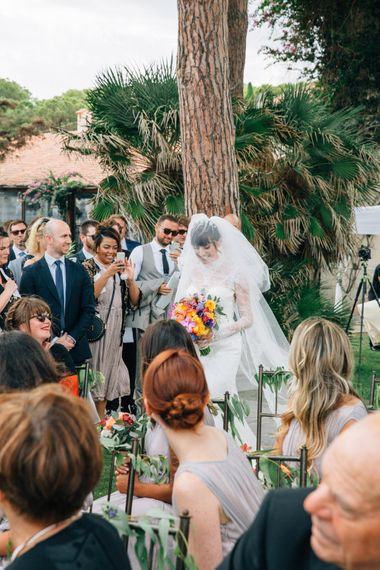 Bridal Entrance in Bespoke Lace Bridal Gown & Veil | Colourful, Sophisticated,  Outdoor Wedding at Is Morus Relais in Southern Sardinia, Italy |  Greg Funnell Photography