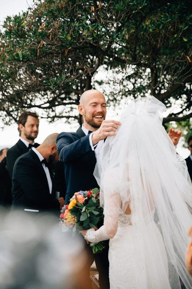 Wedding Ceremony | Bride in Bespoke Lace Wedding Dress | Groom in YSL Tuxedo | Colourful, Sophisticated,  Outdoor Wedding at Is Morus Relais in Southern Sardinia, Italy |  Greg Funnell Photography