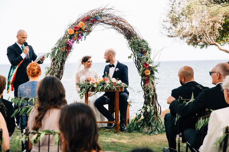 Wedding Ceremony | Floral Arch | Bride in Bespoke Lace Wedding Dress | Groom in YSL Black Tie Suit | Colourful, Sophisticated,  Outdoor Wedding at Is Morus Relais in Southern Sardinia, Italy |  Greg Funnell Photography