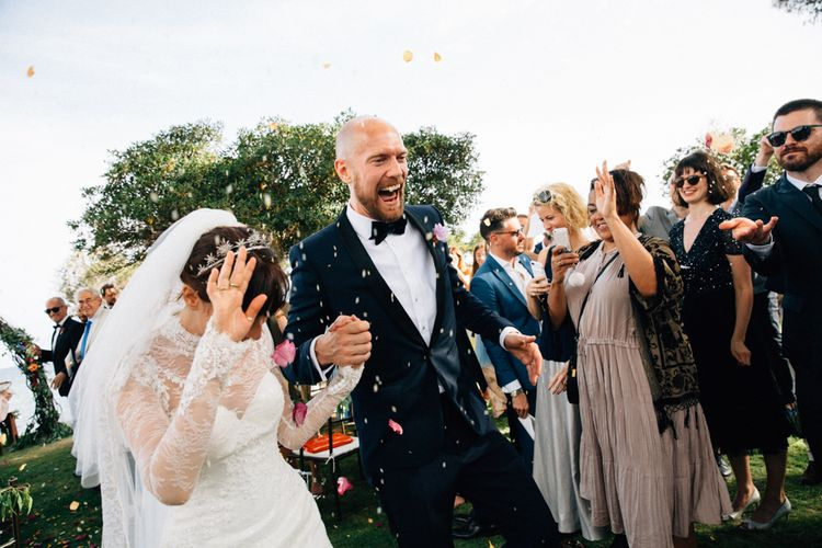 Confetti Exit | Bride in Bespoke Lace Wedding Dress | Groom in YSL Black Tie Suit | Colourful, Sophisticated,  Outdoor Wedding at Is Morus Relais in Southern Sardinia, Italy |  Greg Funnell Photography