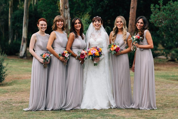 Bridesmaids in Grey Debut Dresses | Bride in Bespoke Lace Wedding Dress | Colourful, Sophisticated,  Outdoor Wedding at Is Morus Relais in Southern Sardinia, Italy |  Greg Funnell Photography