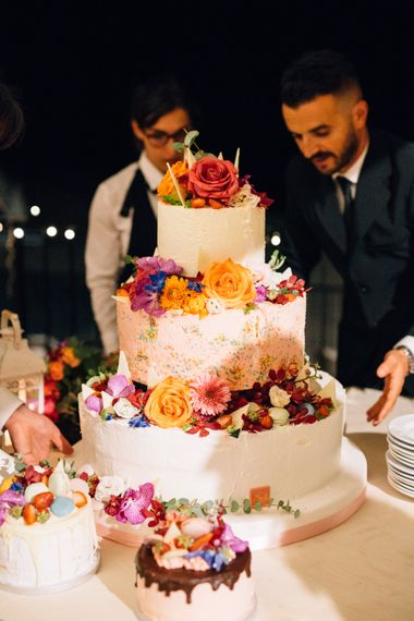 Wedding Cake with Flower Decor | Bride in Bespoke Lace Wedding Dress | Groom in YSL Black Tie Suit | Colourful, Sophisticated,  Outdoor Wedding at Is Morus Relais in Southern Sardinia, Italy |  Greg Funnell Photography