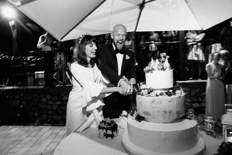 Cutting the Cake | Bride in Ellery Dress | Groom in YSL Black Tie Suit | Colourful, Sophisticated,  Outdoor Wedding at Is Morus Relais in Southern Sardinia, Italy |  Greg Funnell Photography