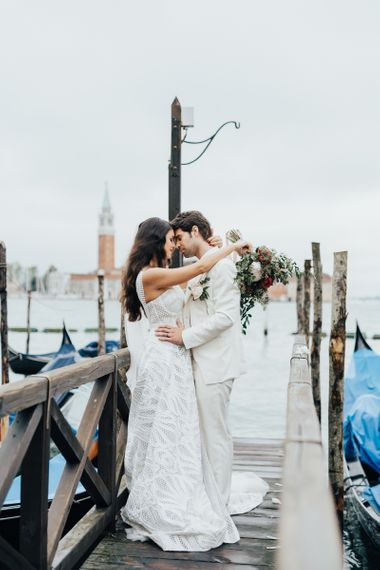 Groom in Ivory Suit and Bride in Applique Wedding Dress Embracing in Venice