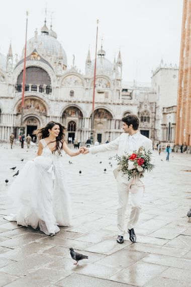 Groom in Ivory Suit and Bridesmaid in Princess Wedding Dress Holding Hands for Venice Elopement