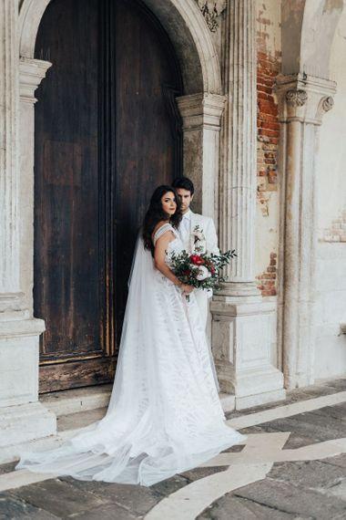 Elegant Bride in Halterneck Wedding Dress  and Groom in White Wedding Suit