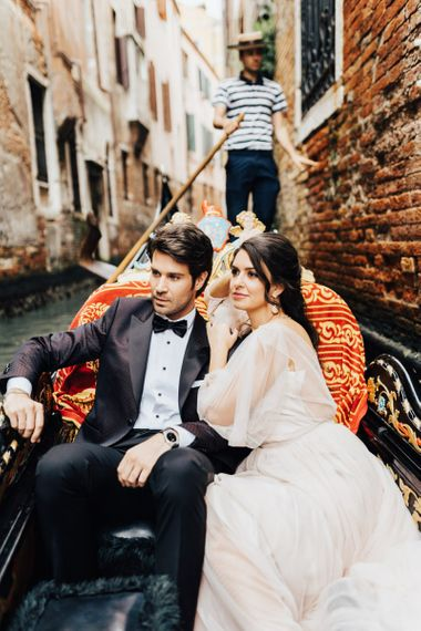 Bride in Tulle Wedding Dress and Groom in Tuxedo Riding a Gondola in Venice