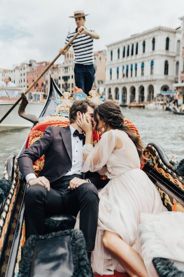 Bride in Tulle Wedding Dress and Groom in Tuxedo Kissing on a Gondola in Venice for Elopement