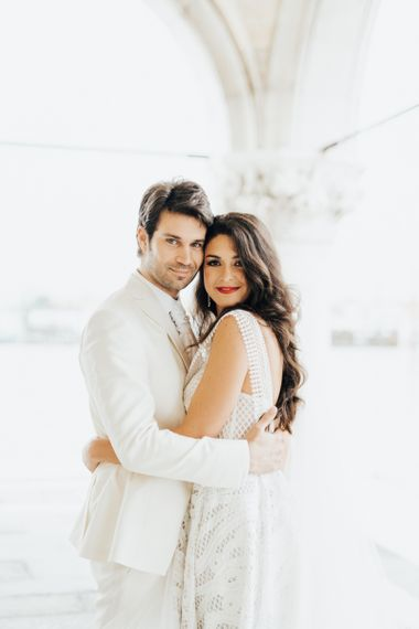 Bride in White Wedding Dress with Wavy Hairstyle and Red Lipstick and Groom in Cream Wedding Suit