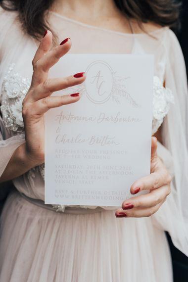 Bride in Tulle Wedding Dress Holding a Vellum Wedding Invitation