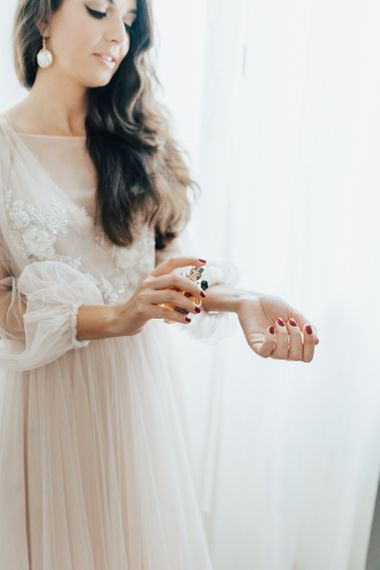 Bride in Blush Pink Tulle Wedding Dress Putting on Perfume