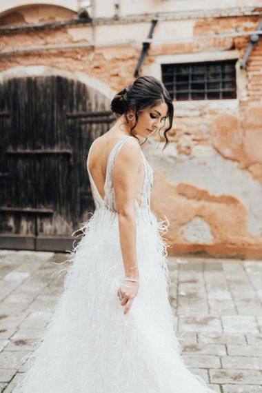 Bride in Sequin and Feather Wedding Dress with Sleek Bridal Updo for Venice Elopement