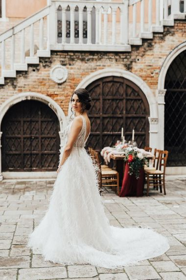 Bride in Sequin and Feather Wedding Dress Standing in Front of a Rustic Tablescape