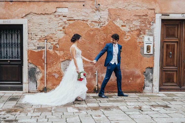 Groom in Navy Suit Holding Hands with His Bride in a Feather Wedding Dress for Venice Elopement