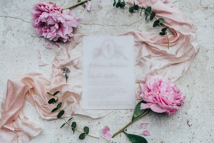 Romantic Vellum Wedding Invitation Surrounded by Ribbons and Peonies