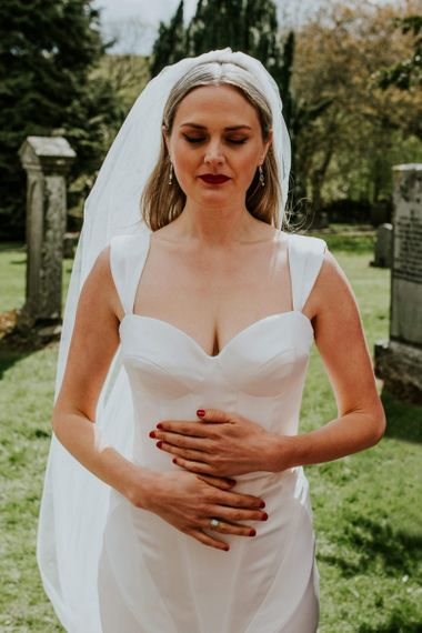 Bride takes a moment in fitted wedding dress before church ceremony