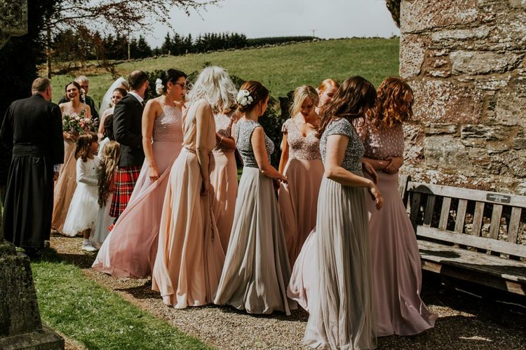 Bridesmaid in mismatched dresses make their way to the ceremony