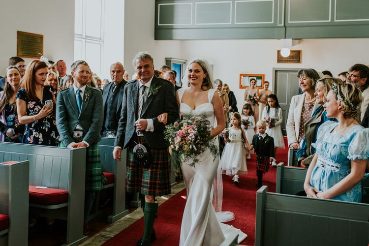 Bride walks down he aisle with father